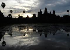 Ancient Skyscrapers: Angkor Wat (mboogiedown) Tags: travel sky reflection water silhouette skyline clouds sunrise asian dawn asia cambodia cambodian khmer culture buddhism places angkorwat palm monsoon siem reap sacred ripples southeast vat spiritual siemreap angkor wat cultural worldheritage kampuchea mapcambodia wondersoftheworld cambogia theravada interestingness497 i500 8906 travelforpeace sugarpalm hinduhism khmeet placestogobeforeyoudie asamazingasangkorwatisitpalesincomparisontothebeautyandresilienceofthecambodianpeople yoake yoakemae ancientskyscrapers theskyscrapersoftheirday camboge beatravelernotatourist dontjustseetheworldexperienceit experiencecambodia buddhistnations