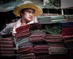 Anxiously selling mats (stormymayen) Tags: mats vendor seller hat anxious thailand sunny street man face scar portrait photography hot warm tropical towel cart