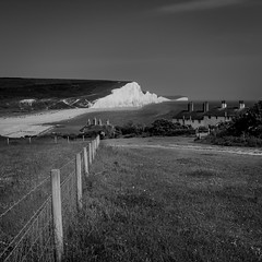 Cuckmere Haven (Lloyd Austin) Tags: cuckmerehaven eastsussex sevensisters england landscape seascape sea fencing fields grass pathway cliffs chalk white black grey light exposure walking coastal coastline coastguardcottages seaview vista view sky beach bw bnw blackandwhite blackwhite mono monochrome composition leadinglines people sigma1750mm d7200 dramatic nikon southdowns southernengland nationalpark