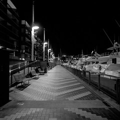 Viaduct  (Film) (Harald Philipp) Tags: harbour harbor auckland newzealand waterfront promenade night blackandwhite bnw bw walkway streetlights pavement boats americascup viaduct dark hasselblad 503 pro400h fuji 6x6 66 120 urban city pedestrian apartments flats