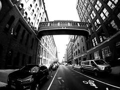 Manhattan Walkway (MassiveKontent) Tags: streetphotography bwphotography streetshot gopro fisheye architecture geometric lines symmetry building bw contrast city monochrome urban blackandwhite streetphoto manhattan shadows nyc newyorkcity skybridge walkway street