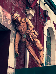 The Wall Support (Steve Taylor (Photography)) Tags: leaning art mannequin contrast blue orange mauve purple white stark eerie spooky weird strange man newzealand nz southisland canterbury christchurch arch window sagging helmet headlaml glows overalls coverall