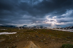 Storm Clouds and Sun Rays over the Sognefjellet (Norway) (briburt) Tags: briburt fuji fujifilm xe1 1855 snow sun orange clouds storm turbulent gray sunrays crepuscular stones mountains sognefjell jotunheimen light summer stark rocks norway norwegian blue glow sky azure panorama dramatic contrast godrays majestic landcape