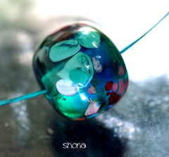 Shona (Laura Blanck Openstudio) Tags: openstudio openstudiobeads glass murano handmade art beads single focal bead fine arts artist artisan round donut nugget big holes shiny bright bold frit whimsical funky odd abstract asymmetric earthy organic made usa boutique upscale boho soho urban chic contemporary transparent translucent one kind jewelry necklace pendant stainless steel choker lampwork published winner show festival teal green bottle pine emerald blue jungle lagoon red coral pink mermaid rose mauve speckles aqua turquoise marine ocean