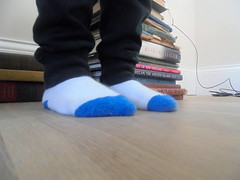 DSC03112 (classroomcamera) Tags: inside indoor indoors sock socks feet foot toe toes blue white clean floor floors flooring wood wooden stand stands standing sit sits sitting book books pile piles stack stacks black pant pants leg legs kid kids child children person people