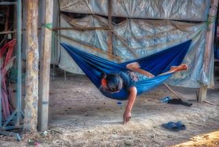 Cambodia, bored girl in hammock