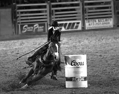 024693763304-97-Cowgirl Barrel Racing at the Clark County Fair and Rodeo-2-Black and White (Jim There's things half in shadow and in light) Tags: 2018 america april clarkcountyfairandrodeo mojave nevada southwest usa desert barrelracing cowgirl sports coors blackandwhite american americana ameica