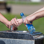 Men filling a plastic bottle with water at a drinking fountain thumbnail