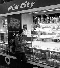 I Will Have A Pasty For My Pecs (tcees) Tags: westendcitycenter budapest hungary pest westernrailwaystation váciút31062 shops mall stores urban x100 fujifilm finepix people stall food pasties drink assistant bw mono monochrome blackandwhite shop