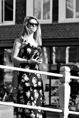 Laura on the Bridge (d_t_vos) Tags: woman spring summer dress sun sunny sunnyday bridge sunglasses arms cleavage monochrome contrast purse wallet keys ballustrade railing bridgerailings street streetphotography streetportrait leeuwarden nieuwestad waagplein langepijp candid portrait laura girl dickvos dtvos