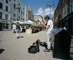 LEEDS STREET PHOTOGRAPHY (Tyrone Fleming) Tags: colourfilm filmphotography gwtphotography ilovefilm ishootfilm kodakportra400 people portra400 tyronefleming leedsstreetphotography buskinginleeds busking buildings road pavement guitar shopping shoppers stalls