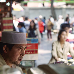 Muslim man watching the street, Muslim quarter, Xian, China (BryonLippincott) Tags: muslimmarket xian china asia asian chinese market portrait en environmentalportrait muslim muslimquarter tourism tourist travel destination street man vendor shopkeeper eyes focused hat taqiyah islam islamic