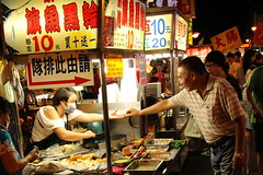 Changing hands (I.M.W.) Tags: taiwan taipei market stall food dinner night evening street light dark hands
