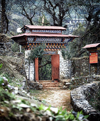 Bhutan: Crossing the Gates. (icarium.imagery) Tags: bhutan canoneos5dmarkiv architecture artwork captureone detail drukyul dzong forest gasavalley gasadzong nature rural sigma100400mmf563dgoshsm tree woodcarving gate buddhist travel path stonewall