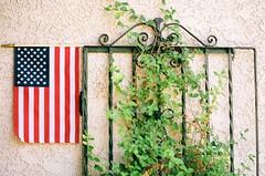 Garden gate (Desertbloom Photography) Tags: desertbloomphotography summertime summer flag manualexposure redwhiteblue outdoors tradition analogue film tamron90mm nikonf100 ektar100 vintage gardengate america americanflag