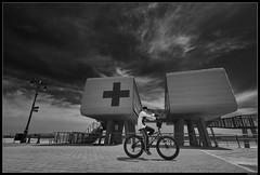 Boardwalk Rider (LilFr38) Tags: lilfr38 fujifilmxpro2 fujinonxf1024mmf4rois fujifilm xpro2 newyork brooklyn coneyisland blackwhite noirblanc boardwalk rider redcross promenade velo croixrouge ridersonthestormthedoors