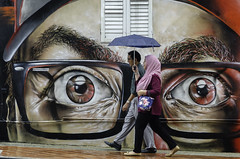 Someone's watching (jeremyhughes) Tags: singapore street people couple headscarf mural art wallart rain raining rainfall umbrella eyes city urban handbag weather nikon d7000 nikkor 18200mmf3556gvr red streetart