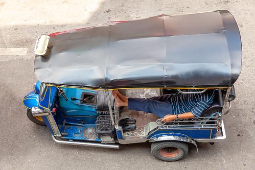 A tuk-tuk driver waits for customers