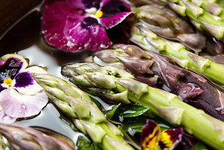 Set of raw white, green, purple asparagus in copper basin with violet and mint. Old wooden rustic background. Organic healthy eating concept. Close up. Overhead.