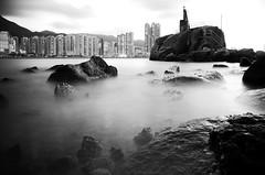 illusory... (Wilson Au | 一期一会) Tags: fujifilm xe2 xf1855mmf284rlmois fujinon hongkong blackandwhite monochrome slowshutter longexposure city buildings sea water rocks lighttower landscape