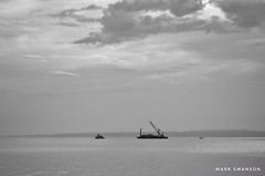 Heading out to work (mswan777) Tags: coast shore seascape ansel white black monochrome 1020mm sigma d5100 nikon work sky cloud island mackinac straits morning water float boat tug crane barge