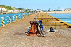 Bike Stand (Geoff Henson) Tags: bicycle bike pushbike bag rucksack jumper pier jetty harbour water sea sky buildings footpath rails capstan rust rusty