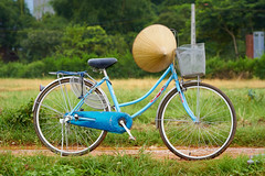 Vietnamese hat resting on a bicycle (BryonLippincott) Tags: vietnam vietnamese vietnameseculture asia asian southeastasia countryside farm farming hanoi agriculture rural ruralscene farmscene farmland rice ricepaddy paddy country industry production growing community one outdoors sunlight vn bicycle vietnamesehat blue basket path road