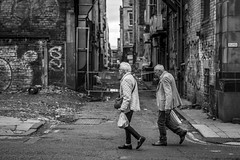 Homeward Bound (Leanne Boulton) Tags: road urban street candid streetphotography candidstreetphotography streetlife sociallandscape urbanlandscape old elderly man woman male female couple walking stride face faces mood atmosphere location alley alleyway decay grit gritty grime dirt rubble graffiti tone texture detail depthoffield bokeh naturallight outdoor light shade city scene human life living humanity society culture people canon canon5d 5dmkiii 70mm ef2470mmf28liiusm black white blackwhite bw mono blackandwhite monochrome glasgow scotland uk