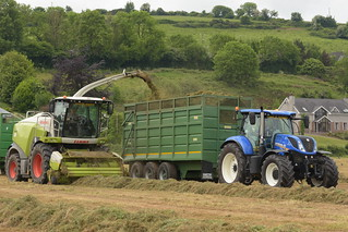 Claas Jaguar 970 SPFH filling a Smyth Field Master Tri-Axel Trailer drawn by a New Holland T7.230 Tractor