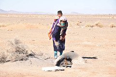 Berber Woman and Child (meg21210) Tags: berber berbere nomad nomads morocco desert sahara home temporary camp encampment fire baby people woman mother child tendingthefire