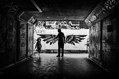 city of angels (Daz Smith) Tags: chosen dazsmith fujixt20 fuji xt20 andwhite bath city streetphotography people candid portrait citylife thecity urban streets uk monochrome blancoynegro blackandwhite mono bristol bearpit silhouette father child angel graffiti mural wings