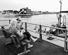 BenchBuddies (Hodd1350) Tags: mudeford mudefordquay christchurch dorset blackhouse fishingboat women females bench sitting railings seawater harbour shore leica leicaq bw wb blackwhite whiteblack mono