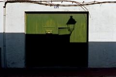 El farol (Gabo Barreto) Tags: menorca balearicislands baleares 35mm film kodak ektar shadow garage gate door lantern lamp shapes analoguephotography filmisnotdead ishootfilm 135 vivitar35es rangefindercamera c41 colourfilm green santlluis sanluis