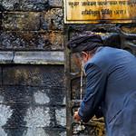 man washing at one of the stone water spouts at the Shree Pashupatinath Temple, Kathmandu, Nepal thumbnail