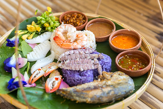 Beautiful set of Thai Food - Colorful steamed rice served with seafood and various spicy paste and sauce, bamboo table background.
