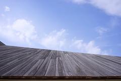 Naoshima Hall (Eric Flexyourhead) Tags: honmura naoshima 直島 naoshimacho 直島町 kagawa kagawaken kagawaprefecture 香川県 setonaikai 瀬戸内海 setouchi japan 日本 naoshimahall hiroshisambuichi sambuichihiroshi building architecture roof rooftop wood wooden sky blue bluesky blueskies clouds soft puffy sonyalphaa7 zeisssonnartfe35mmf28za zeiss 35mmf28