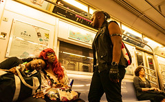 The Subway to Comic Con (UrbanphotoZ) Tags: subway 7train comiccon couple resting redwig man standing leather blackleather mohawk gloves armband spikes woman sitting flushingline zola anythingforlove freeweddingwebsites redbull farwestside manhattan newyorkcity newyork nyc ny