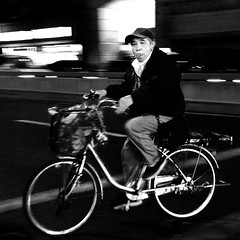Who's watching who? (cresting_wave) Tags: iphoneography mobileography iphonephotography mobilephotography streetphotography nightphotography blackwhite iphonex procamera snapseed bicycle cyclist man intentionalcameramovement camerapanning transportation