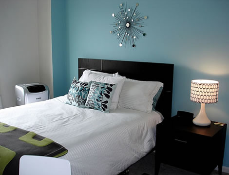 blue walls; rounded black and white lamp; modern silver wall décor