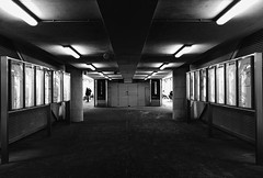 Darkness With Lights (tcees) Tags: stratfordinternational stratford e15 platform pillars roof ceiling light shutter map timetable people man woman bw mono monochrome blackandwhite seat bench x100 fujifilm finepix trainstation waitingarea floor building architecture urban uk