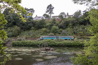 Train by the water's edge: River Taff, Radyr, Cardiff
