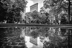 It's Your World (Thomas Hawk) Tags: america flatiron flatironbuilding fullerbuilding manhattan nyc newyork newyorkcity usa unitedstates unitedstatesofamerica architecture bw park reflection fav10 fav25 fav50 fav100