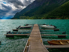 Boat Dock at the End of the Lustrafjord (Norway) (briburt) Tags: briburt olympus em5 em5ii microfourthirds micro43 14mm wideangle fjord green aqua lustrafjord sognefjord skjolden storm sunray crepuscular sun water glacial summer mountains light stark norway norwegian blue glow sky azure panorama dramatic contrast majestic turbulent boat forest trees sognogfjordane landscape eide mountain