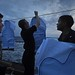 180720-N-HV059-1055 PHILIPPINE SEA (July 20, 2018) Sailors aboard the Arleigh Burke-class guided-missile destroyer USS Mustin (DDG 89) set up shooting targets for a 9mm pistol gun shoot on the ship's flight deck. Mustin is forward-deployed to the U.S. 7th