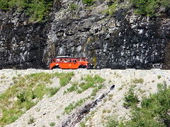Red Tour bus and Weeping Wall (jb10okie) Tags: nps nationalparks vacation usa mountains summer rockymountains worldheritagesite 2016 trip montana glaciernationalpark watertonglacierinternationalpeacepark