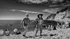 Old fashioned fun. (Neil. Moralee) Tags: beerdevonneilmoralee neilmoralee beach fun man woman old aged elderly mature laughng holdiday hat sun glasses pebbles beer devon uk high contrast push process black white mono monochrome neil moralee nikon d7200 seside british summer heat wave sea shore ocean water waves cliff chair deck deckchair couple duo two pair husband wife lover