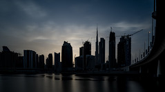 The Low Key Town... (Aleem Yousaf) Tags: dubai united arab emirates alabraj street business bay canal water reflections skyline silhouette low key town downtown metal steel long design middle east walking texture outside style exposure nikon d810 dark sky clouds dxb nikkor lee filter flickr burj khalifa damac properties wide angle city cityscape