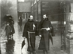 """Two unidentified Franciscan friars walking alongside a church carrying an umbrella"" is Fathers Bibby and O'Connor (National Library of Ireland on The Commons) Tags: republicanphotographcollection nationallibraryofireland franciscan friars church umbrella ireland albertbibby dominicoconnor priests boy capuchinorder churchstreet dublin capuchins warofindependence arrest robes"