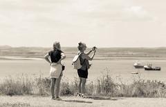 VISITORS to LINDISFARNE (HOLY ISLAND), NORTHUMBERLAND_DSC_0823_LR_2.5 (Roger Perriss) Tags: lindisfarne d750 ladies visitors holyisland northumberland walking photo lightroom lrpreset lr creamtone creamtonepreset blackandwhite monochrome mono takingphotograph takingphoto photograph photographer girls women lindifarneharbour harbour boats boatsinbackground mainland island