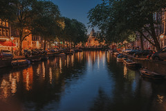 Amsterdam (Mark Liddell) Tags: amsterdam holland thenetherlands netherlands nederlands capital city europe travel canal night water reflections vangogh vincentvangogh boats still peaceful romantic royal streets trees car long exposure canopy shops storefront stores twilight dusk summer
